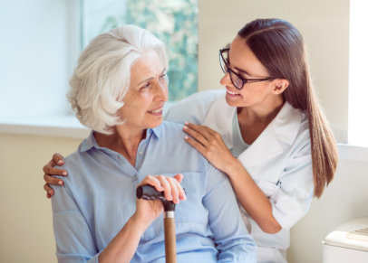 elder woman and her caregiver smiling at each other