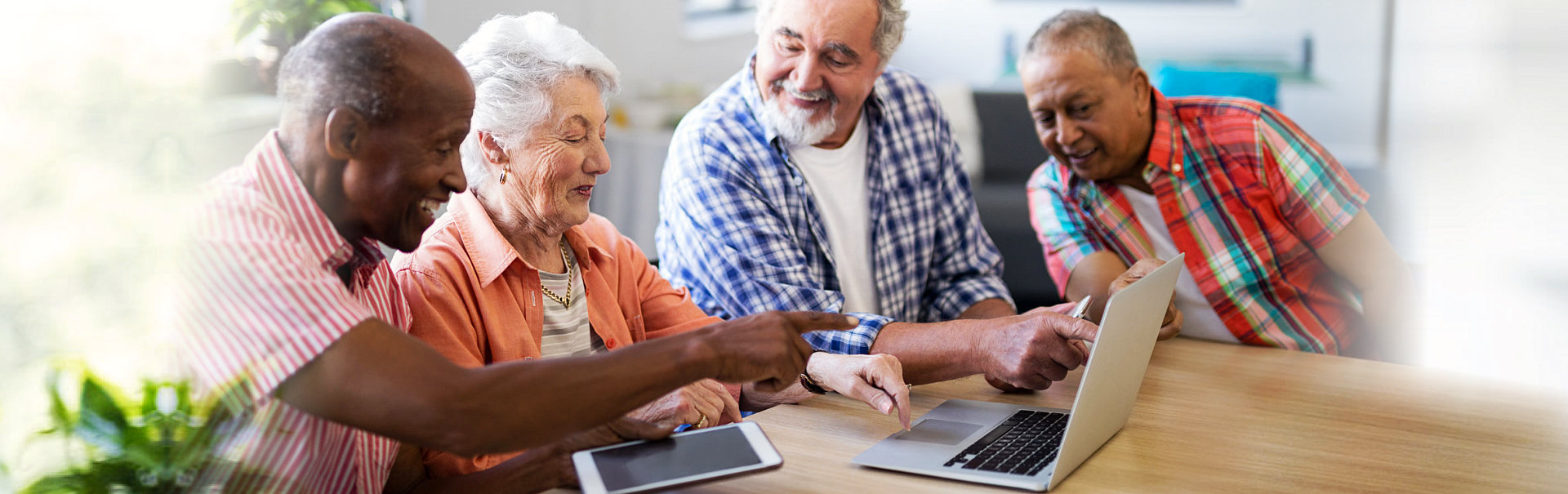 group of elderlies using a laptop and a tablet