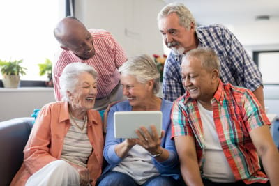 Senior women showing digital tablet to cheerful friends while sitting on sofa at nursing home